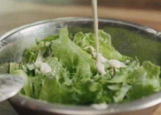 closeup mixing frillis salad leaves with caesar sauce